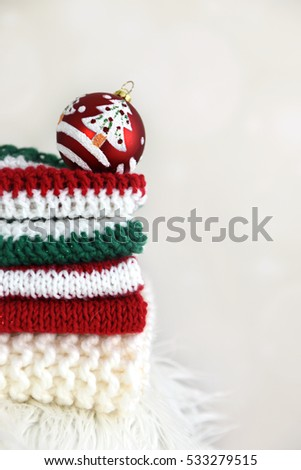 A pile of folded handmade crochet and knit clothes with a Christmas ball