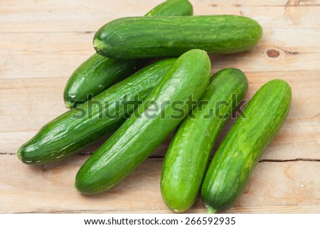 a pile of fresh picked cucumbers on wooden background - stock photo