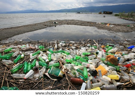 a pile of garbage and plastic bottles on the lake shore - stock photo