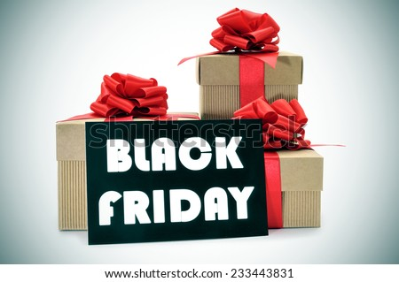 a pile of gift boxes tied with red ribbon and a black signboard with the text black friday written in white - stock photo