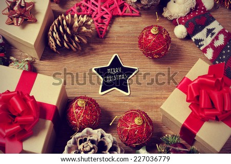 a pile of gifts and christmas ornaments, such as christmas balls and stars, on a rustic wooden table with a heart-shaped chalkboard with the text merry christmas in the center - stock photo