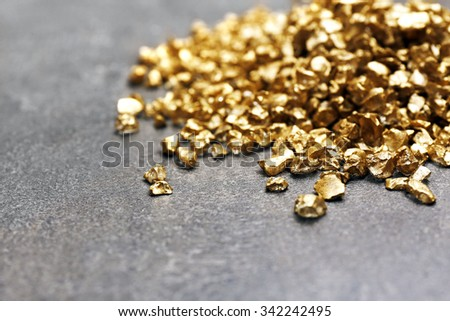 A pile of Gold nugget grains, on cement background - stock photo