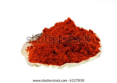 a pile of ground paprika on a sea shell, isolated on white, bright red color, sharp shot.