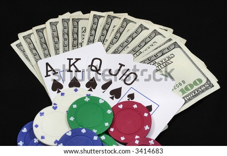 A pile of large money bills, royal flush, and poker chips. - stock photo