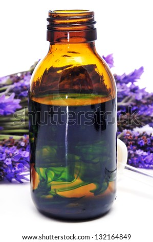 a pile of lavender flowers and a dropper bottle with lavender essence - stock photo