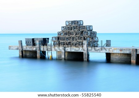 A pile of lobster pots, stacked on a jetty. Swanage, Dorset - stock photo
