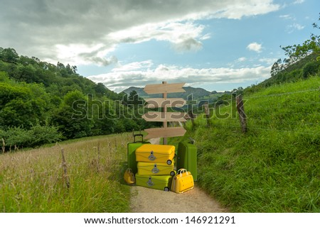 A pile of luggage with directional signs pointing everywhere in the middle of the countryside - stock photo