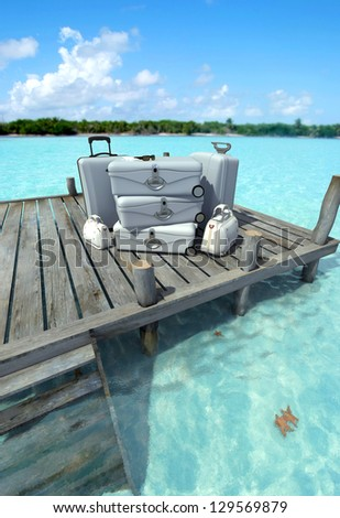 A pile of luxurious luggage standing by the pier on a tropical landscape