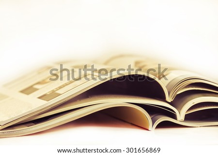 a pile of magazines close up on white background