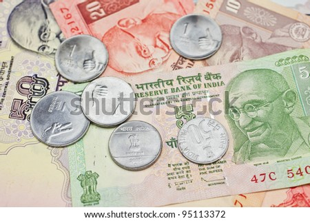 A pile of notes and coins in Indian currency. - stock photo
