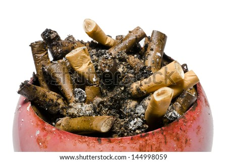 A pile of old and fresh cigarette butts in old, rusty, red ashtray. - stock photo