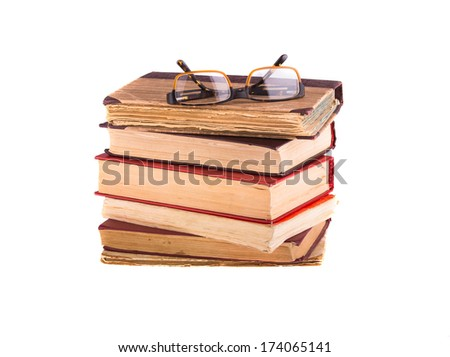 A pile of old books and glasses, isolated on white background. - stock photo