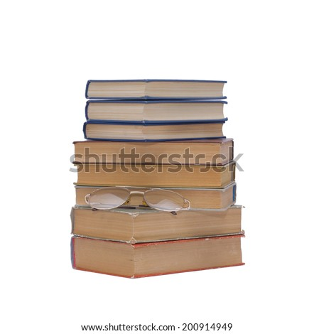 A pile of old books and glasses isolated on white background - stock photo