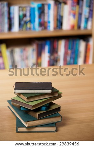 A pile of old books on a table, with shelves of books in the background. - stock photo