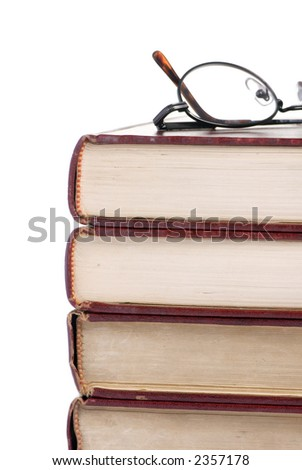 A pile of old books with a pair of glasses on the top - stock photo