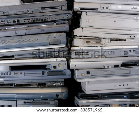 A pile of old, broken, and dusty laptops in a pile for recycling. The laptops are dirty, and many are missing pieces. Focus point is the VGA port on the laptop in the middle. - stock photo