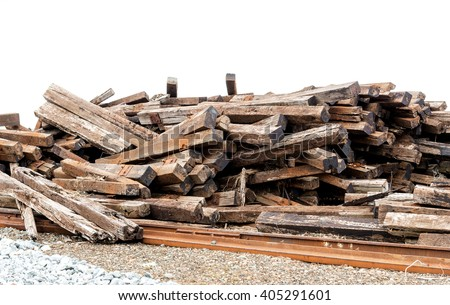 A pile of old, rotting, and broken railway ties. The sky in the background is cloudy. Some old, rusty rail is in front of the pile, Focus is in the middle. There is room for text. - stock photo