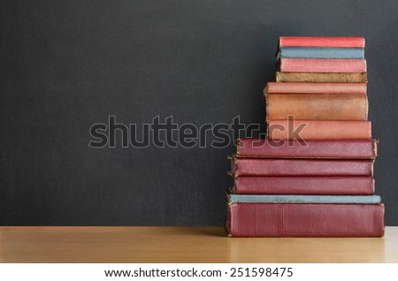 A pile of old, shabby, well used text books stacked in a pile on a wooden desk in front of a black chalkboard.  Copy space on left side. - stock photo