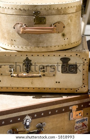 A pile of old suitcases well worn with hints of where they have been. - stock photo