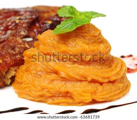 A pile of orange sweet potato puree with a mint leaf on top (Selective Focus, Focus on front of the puree and the front leaf) - stock photo