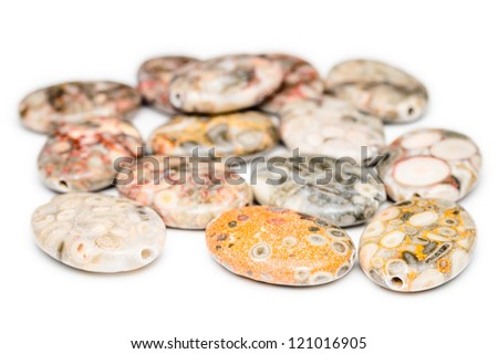 A pile of oval and colorful fossil jasper beads with holes drilled through them. Nice patterns on these beads. - stock photo