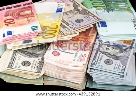 A pile of paper money three currencies (dollars, euros, rubles) on a black background - stock photo