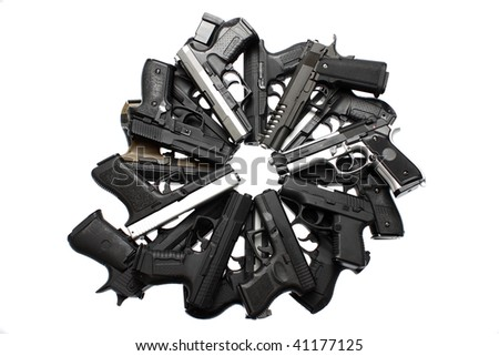 A pile of pistols on a table. - stock photo