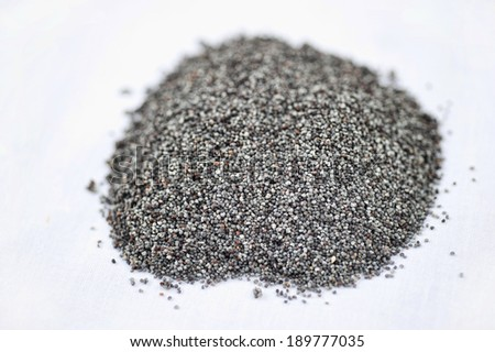 A pile of Poppy seeds spread on a white background on a sunny day.