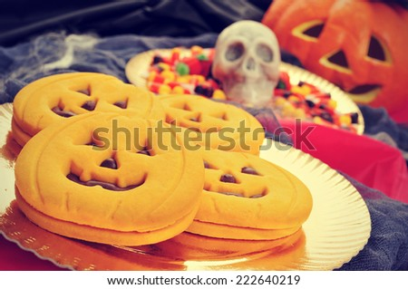 a pile of pumpkin-shaped cookies and some different Halloween candies with scary ornaments in the background, such as a skull, cobwebs or a jack-o-lantern - stock photo