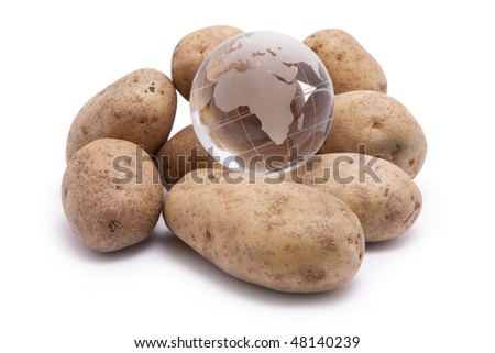 A pile of raw potatoes with a world globe on top.  Conceptual image for world hunger, feeding the world, etc. - stock photo