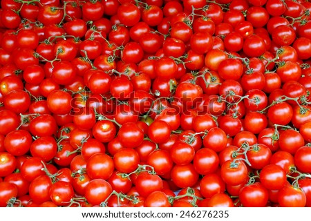 A pile of Red Cherry Tomatoes on a stand at the Market