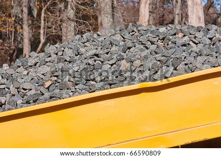 A pile of rocks in a yellow wagon to be used in a construction project