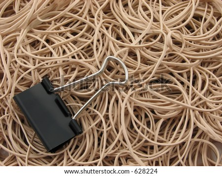 A pile of rubber bands and a single offset butterfly binder clip - stock photo