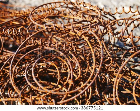 A pile of rusty, discarded, old couch springs on the ground in an empty lot. - stock photo