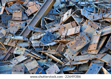 A pile of scrap metal left from replacing the rails on a railroad. Shallow depth of field with focus on center of frame. - stock photo