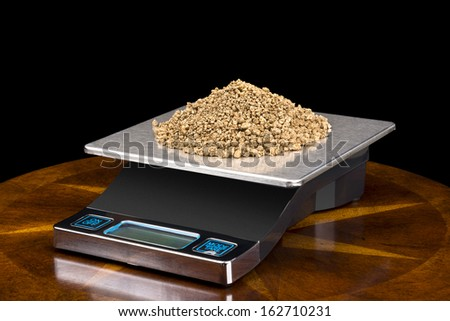 A pile of small gold nuggets on a scale being weighed for their investment value. - stock photo
