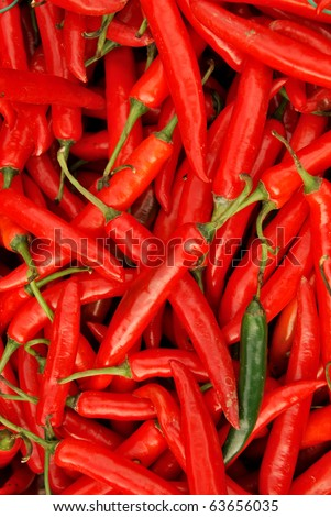 A pile of spicy red hot chili peppers and one green pepper in corner