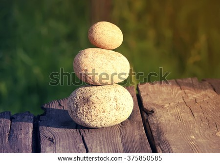 A pile of stones stacked on wooden table outdoors. - stock photo