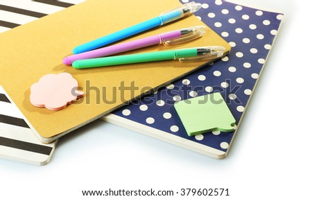 A pile of stylish notebooks and stationary, isolated on white background - stock photo