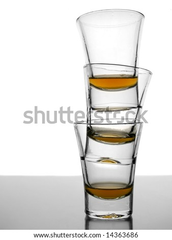 A pile of three almost empty shots of whiskey on white background over gray floor. - stock photo