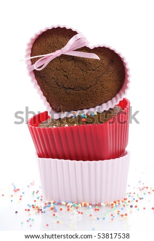A pile of three chocolate heart shape muffins in  silicone molds with strawberry and sprinkles - stock photo