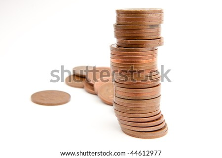 A pile of two pence pieces with some more coins scattered in the background.  Focus on the stack.