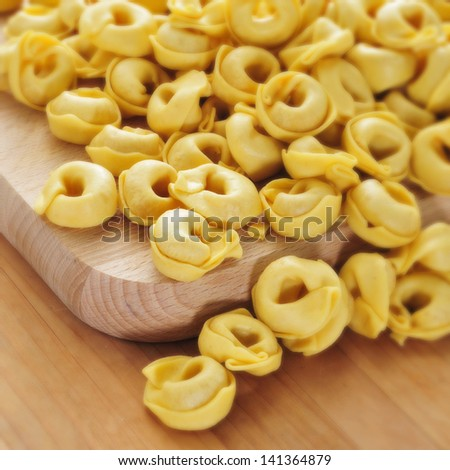 a pile of uncooked tortellini on a table, ready to be boiled - stock photo