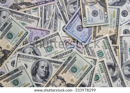 A pile of  US dollar bills on a table pile as background. - stock photo