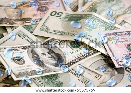 A pile of US dollars with blue water droplets on them.  Great concept for money laundering or rainy day savings spending. - stock photo