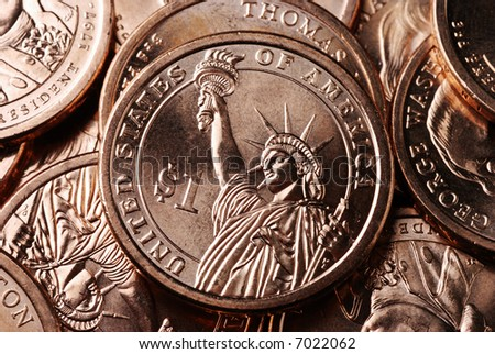 A pile of US presidential dollar coins with the focus on one coin showing the reverse side featuring the Statue of Liberty. - stock photo