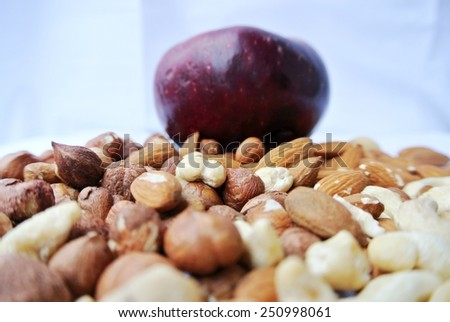 A pile of various nuts with a red apple in the background. Healthy/clean eating concept. - stock photo