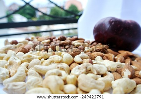 A pile of various nuts with a red apple in the background. Healthy eating concept. - stock photo