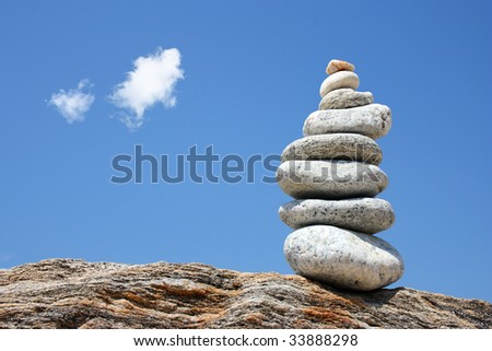 a pile of white stones on a rock, blue sky with small white clouds in the background - stock photo