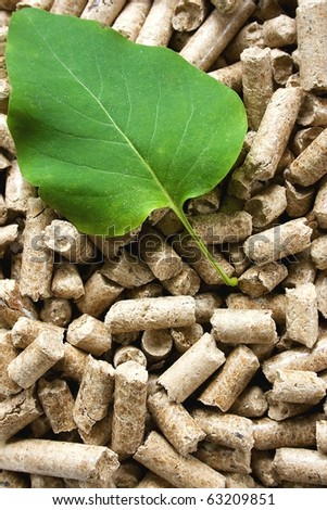 A pile of wood pellets with a green leaf - stock photo